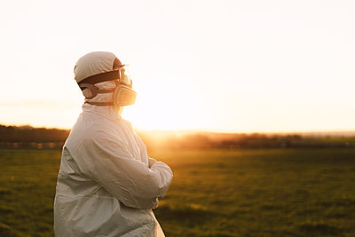 Man wearing protective suit and mask in the countryside at sunset - p300m2166409 by Eloisa Ramos