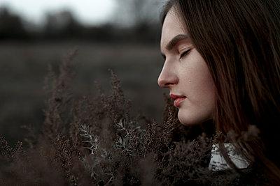 Caucasian woman smelling foliage - p555m1219690 by Vyacheslav Chistyakov