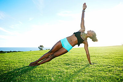 African American woman practicing yoga in park - p555m1411323 by Peathegee Inc