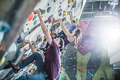 Athletes climbing rock wall in gym - p555m1411960 by John Fedele