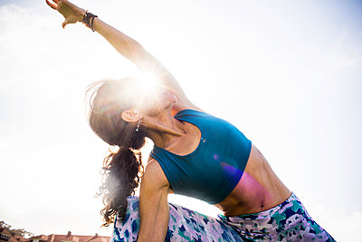 Low angle view of Hispanic woman practicing yoga outdoors - p555m1412132 by Adam Hester