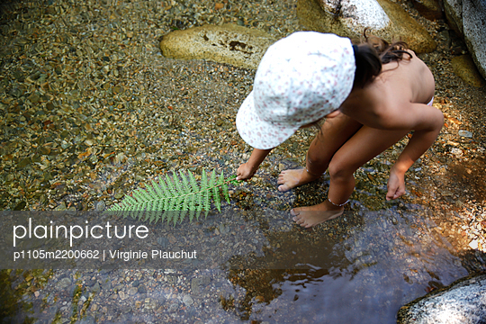 Little girl playing with fern leaf in a river - p1105m2200662 by Virginie Plauchut