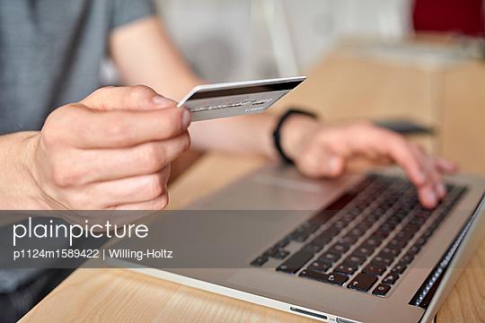 Junger Mann am Laptop mit Kreditkarte - p1124m1589422 von Willing-Holtz