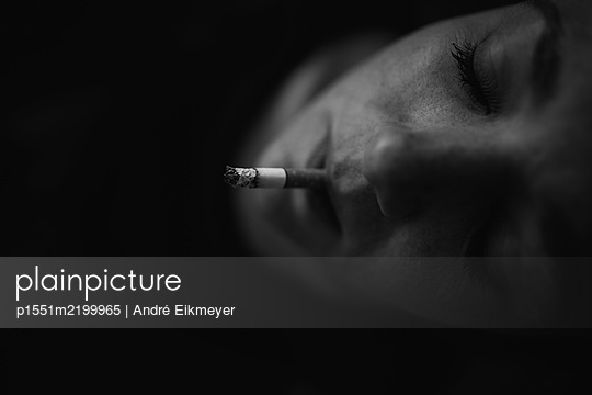 Womn smoking a cigarette, close-up - p1551m2199965 by André Eikmeyer