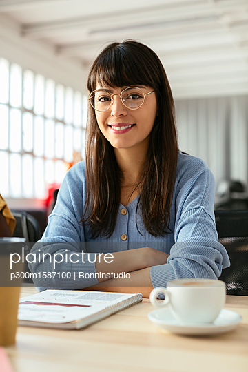 Portrait of smiling young woman with notepad at desk in office - p300m1587100 von Bonninstudio