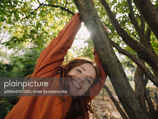 Happy redheaded woman enjoying autumn in a park - p300m2167253 by Kniel Synnatzschke