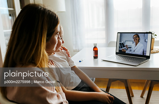 Mother and daughter listening to doctor on video call over laptop at home - p300m2275998 by Marco Govel