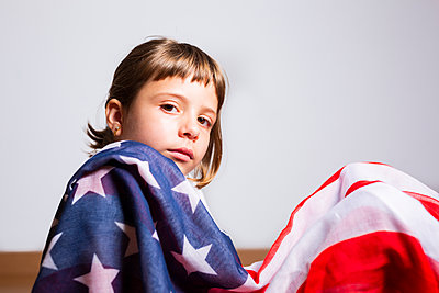 Beautiful portrait of a 6-year-old blonde girl wrapped in the American flag - p1166m2193948 by Cavan Images