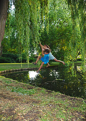 Children swinging on a branch of a weeping-willow above a pond - p1231m2191451 by Iris Loonen