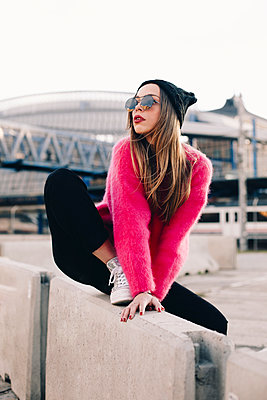Portrait of fashionable young woman wearing sunglasses, cap and pink knit pullover - p300m2078657 by Aitor Carrera Porté