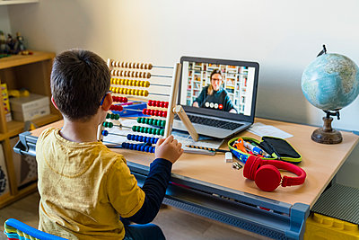 Boy using abacus with teacher on video call during homeschooling - p300m2198688 by Giorgio Magini