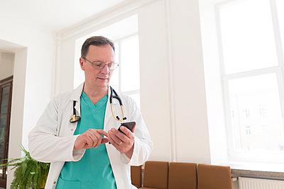 Doctor using smartphone on corridor - p300m2250276 by Hernandez and Sorokina