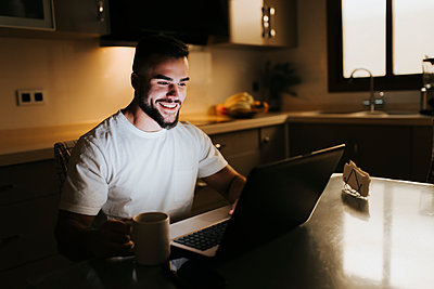 Bearded male entrepreneur having coffee cup while working on laptop at dining table in kitchen - p300m2256284 by Miguel Frias