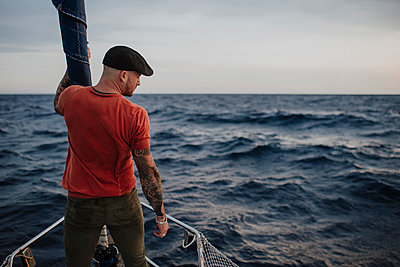 Hipster man looking away while standing on boat in sea during vacation - p300m2276527 by Gala Martínez López