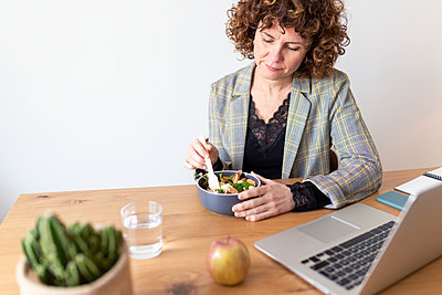 Mature female freelancer sitting at table with laptop having food at home - p300m2282096 by Sus Pons