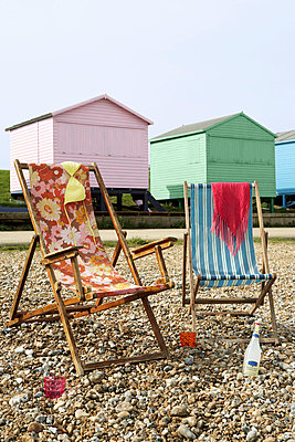 Two deck chairs on a pebble beach with colourful beach huts behind - p3493146 by Jon Day