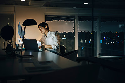 Dedicated male entrepreneur reading document while working late in dark coworking space - p426m2194738 by Maskot
