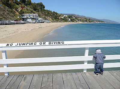 Toddler looking over railing on pier - p42917058 by JLPH
