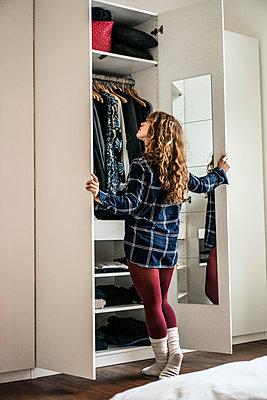 Junge Frau steht vor einem Kleiderschrank - p586m1144034 von Kniel Synnatzschke