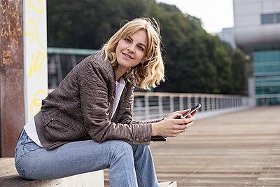 Junge Frau mit einem Smartphone - p788m1466156 von Lisa Krechting