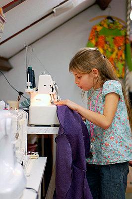 Girl uses sewing machine - p896m834672 by Richard Brocken