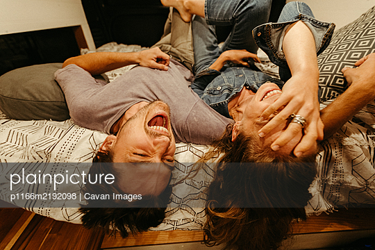 engaged couple relax and laugh lying upside down on their van bed - p1166m2192098 by Cavan Images