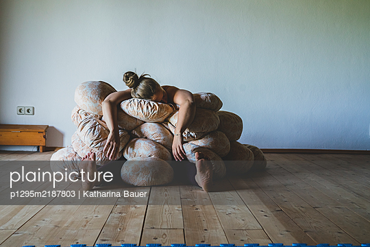 Woman under yoga bolsters - p1295m2187803 by Katharina Bauer
