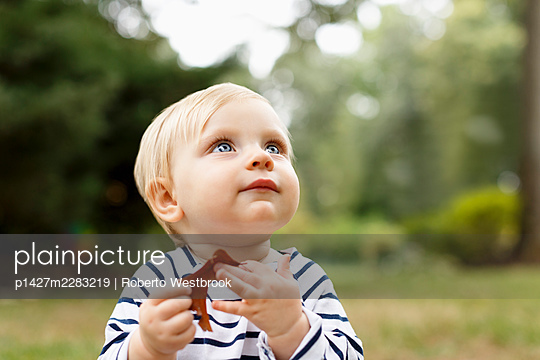 Portrait of baby girl sitting on outdoors - p1427m2283219 by Roberto Westbrook