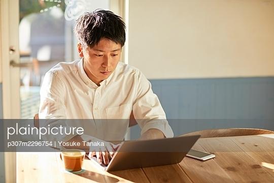 Young Japanese man at a cafe - p307m2296754 by Yosuke Tanaka