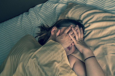 Young woman in bed. - p1072m1022084 by Peter Glass