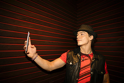 Confident, cool male millennial taking selfie with camera phone in nightclub - p1192m1583715 by Hero Images