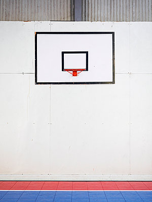 Empty basketball court with basketball hoop hanging on wall - p1427m1553553 by WalkerPod Images