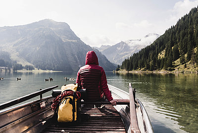 Austria, Tyrol, Alps, woman in boat on mountain lake - p300m1505656 by Uwe Umstätter