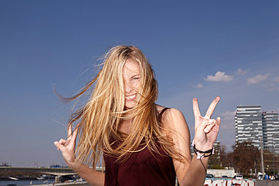 Happy young woman making peace sign - p300m929871f by Jo Kirchherr