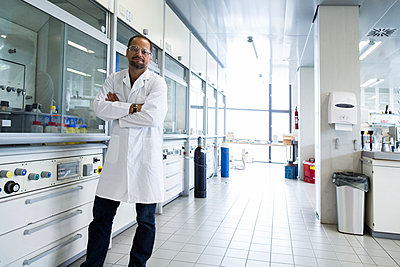 Chemist with crossed arms standing at a laboratory - p300m975390f by Sigrid Gombert
