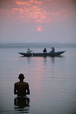 Boat passing a man standing in the holy river , River Ganges (Ganga), Varanasi (Benares), Uttar Pradesh state, India, Asia - p8710233 by Gavin Hellier