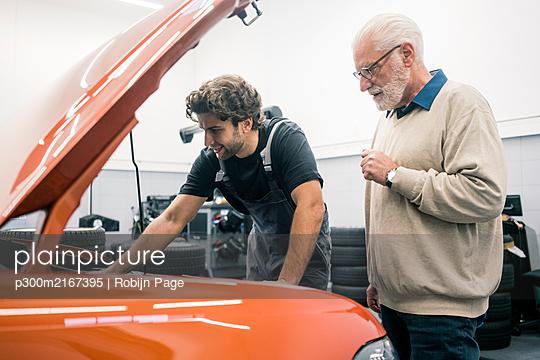 Car mechanic talking to client in workshop - p300m2167395 von Robijn Page