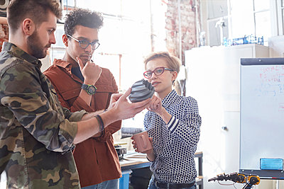 Designers meeting, examining prototype in workshop - p1023m1486419 by Rafal Rodzoch