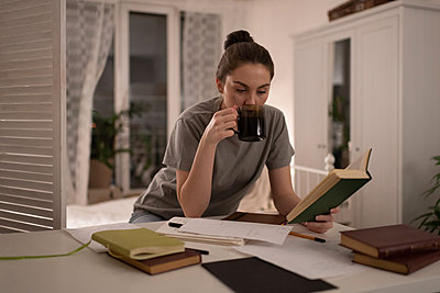 Student reading book and drinking coffee during exam preparation - p1166m2236273 by Cavan Images