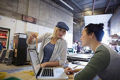 Female design professional engineers brainstorming at laptop in workshop - p1192m1202057 by Hero Images