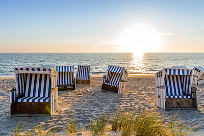 Germany, Schleswig-Holstein, Sylt, beach and empty hooded beach chairs at sunset - p300m1587693 by Ega Birk