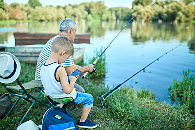 Little boy sitting with grandfather at lakeshore testing smartphone - p300m2023823 von Zeljko Dangubic
