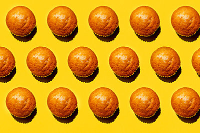 Pattern of rows of muffins against yellow background - p300m2198401 by Gemma Ferrando