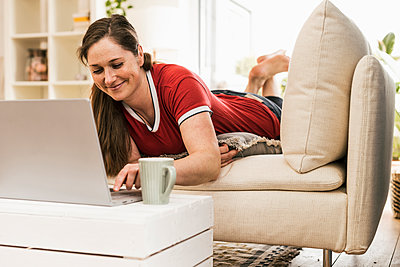 Mid adult woman using laptop while lying on sofa in living room - p300m2268228 by Uwe Umstätter