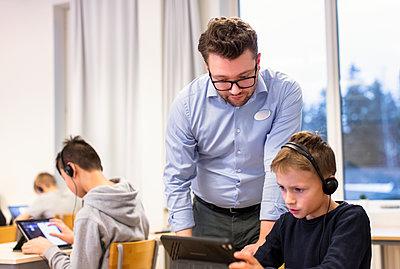 Teacher with schoolboy in classroom - p312m2174462 by Scandinav