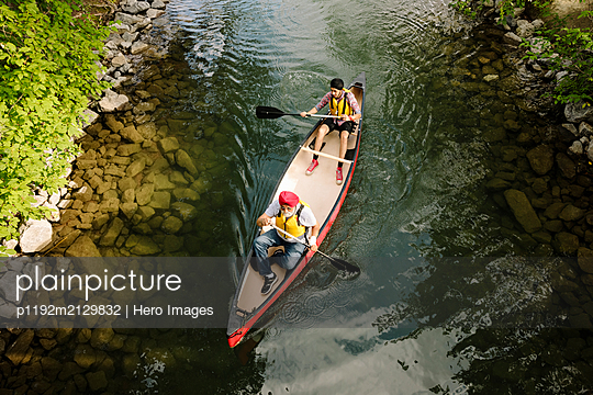 Overhead view of two men canoeing on river - p1192m2129832 by Hero Images