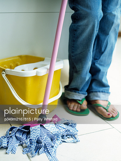 Woman in flipflops with mop and bucket - p349m2167815 by Polly Wreford