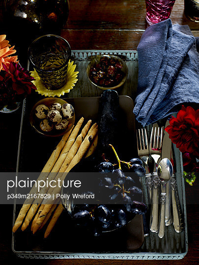 Tray with breadsticks and grapes on wooden table - p349m2167829 by Polly Wreford