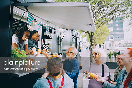 Smiling male and female customers talking to food truck owners in city - p426m2213311 by Maskot