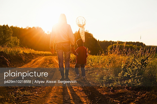 Rear view of father and son with butterfly net walking along dirt track at sunset, Sarsy village, Sverdlovsk Region, Russia - p429m1021855f by Aliyev Alexei Sergeevich